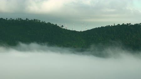smokey : Misty valley and layers of tropical mountain With Wind turbine on top at khao kho , Thailand