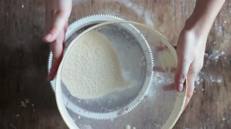 sieving : Top view of woman sieving flour in plate