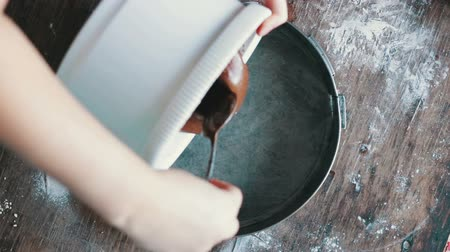 оладья : Top view of woman pours a chocolate dough in a baking tray