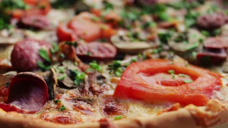 short clip : Pizza with hunting sausage, tomato, herbs and cheese close up view