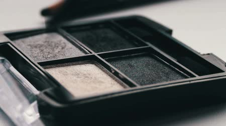 cienie do powiek : Gray shades of eyeshadow,Close up of makeup brush moving over eye shadows