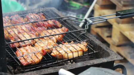 being cut up : Barbecue With Delicious Grilled Meat On Grill. Barbecue Party. Chicken meat pieces being fried on charcoal grill .Cooking delicious juicy meat steaks on the grill on fire.