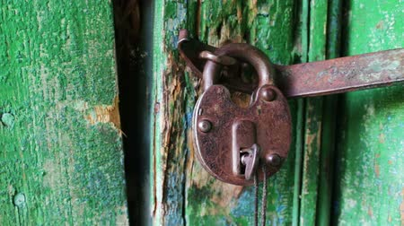 защелка : Beautiful, vintage, old, large, iron lock hangs on the door with wiped paint and old key.Door bolted with a padlock. The door lock is rusty and bolted with a big padlock.