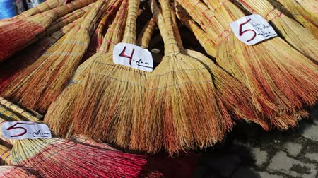 besom : Many brooms lie on counter of the market with a price tag