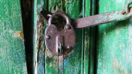 защелка : Old vintage iron lock on the door with a green paint peeled. with keys sticking out in it close up view Стоковые видеозаписи