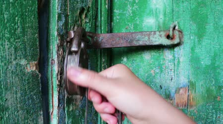 защелка : Old vintage iron lock on the door with green paint peeled. Female hand opens and closes lock Стоковые видеозаписи