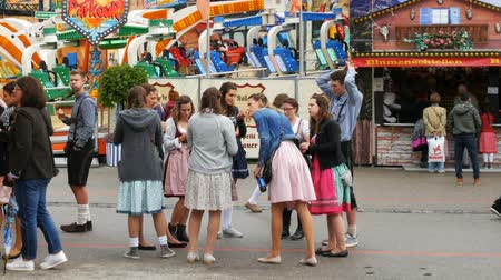 pretzel : September 17, 2017 - Munich, Germany:Crowd of people in national Bavarian suits Dirdl and Lederhose are walking along streets of Teresienvise near attractions and trays with food and sweets