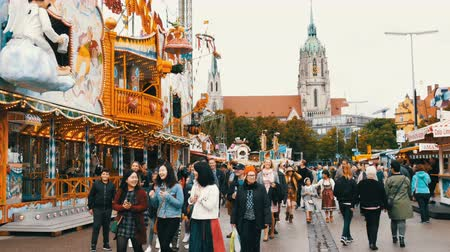 decadência : September 17, 2017 - Munich, Germany: The largest beer festival in a world Oktoberfest. People in national Bavarian suits Lederhose and Dirdln walk around amusement rides at Theresienwiese