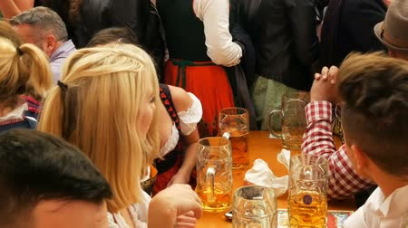 renowned : September 17, 2017 - Munich, Germany:A large number of glass beer mugs filled with beer. People rest on the Oktoberfest, the world-famous festival in Bavaria