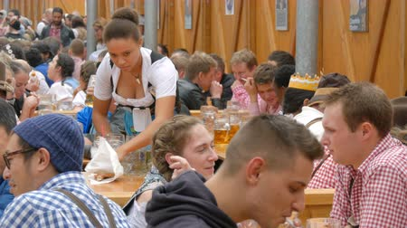pretzel : September 17, 2017 - Oktoberfest, Munich, Germany:Lot of people are sitting in birgarten drinking beer from beer mugs communicate and have fun Stock Footage