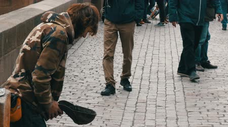 indigence : September 12, 2017 - Prague, Czech Republic: The poor man begs alms in the streets of the city around there are many people and no one gives anything,Beggar sitting in the street waiting for coins