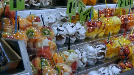 mangosteen : September 22, 2017 - Barcelona, Spain, Mercator de la Boqueria Food Market: a huge counter with tropical fruits, mangoes, passion fruit, kiwi, bananas in plastic packaging