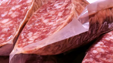 italian speciality : Delicious fresh salami sausages hang on the meat butcher market counter close up