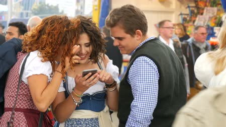 literário : September 17, 2017 - Oktoberfest, Munich, Germany: Extraordinarily beautiful girls in national bavarian suits dirdl smile and look at the smartphone in crowd of people Stock Footage