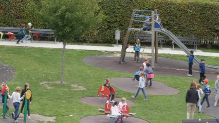 kiddy : September 12, 2017 - Prague, Czech Republic: Many children walk in the playground, ride the rides, swings, slides down to sit on the bench, laughing in the kindergarten in the center of Prague