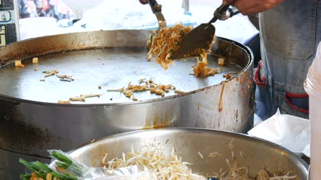 shellfish dishes : Seller of street food fries traditional thai rice noodles with eggs, chicken and sprouts. Asian street food