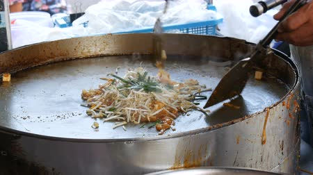 kuşkonmaz : Seller of street food fries traditional thai rice noodles with eggs, chicken and sprouts. Asian street food