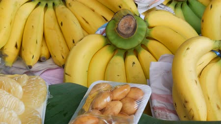 Канчанабури : Beautiful yellow bunches of small bananas on and other exotic fruits on street market counter, Thailand Стоковые видеозаписи