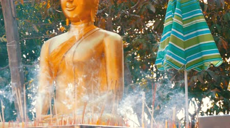 клык : PATTAYA, THAILAND - December 18, 2017: Many delicate aroma sticks of a good luck stand and haze in front of the Buddha statue. Hill of the Great Buddha, Pattaya Стоковые видеозаписи