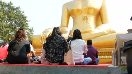 feng : PATTAYA, THAILAND - December 18, 2017: People sit and pray in front of huge Buddha statue. Big Golden Buddha statue on Pratumnak Hill in Pattaya, Thailand