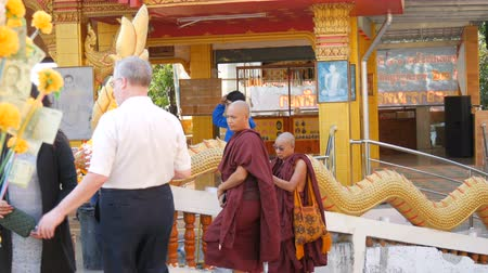клык : PATTAYA, THAILAND - December 18, 2017: Monks and tourists walk along the Buddhist complex Great Buddha Hill
