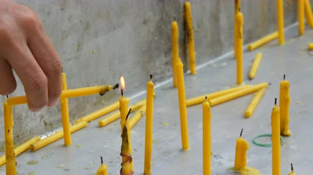 клык : Thin yellow wax candle lights another candle with its flame. Many thin yellow wax candles
