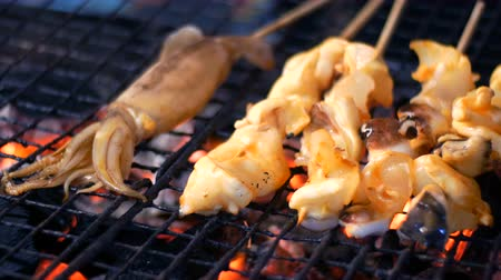 tofu : Night market, Pattaya, Jomtien. Squid grilling on a grill. Thai cuisine. Asian exotic dishes on the market Stock Footage