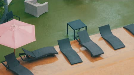 meteoroloji : Stylish black wicker chaise lounges in hotel drip in the pouring rain. Tropical Rainfall in Asia Stok Video