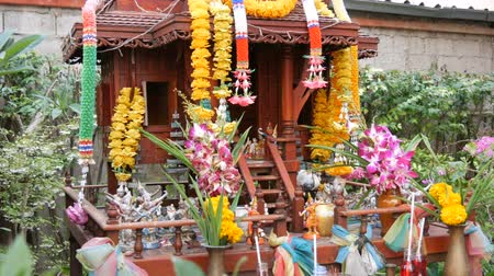 buddhista : Traditional Buddhist altar in the garden in Thailand, decorated with flowers and various symbolic figures. Cat of red color sits on the altar