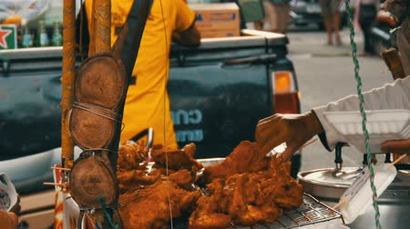 ekmekli : PATTAYA, THAILAND - DECEMBER 17, 2017: Street food of Thailand. Fried chicken pieces in batter.The seller on the street is selling an exotic dish