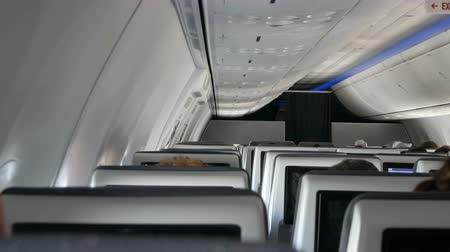 aircraft cabin : Passengers in comfortable seats of aircraft with maps on screens in chairs