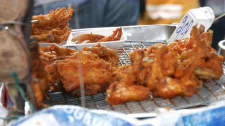 rántott : Street food of Thailand. Fried chicken pieces in batter.The seller on the street is selling an exotic dish. The buyer selects a piece of meat with the help of special tongs for food Stock mozgókép
