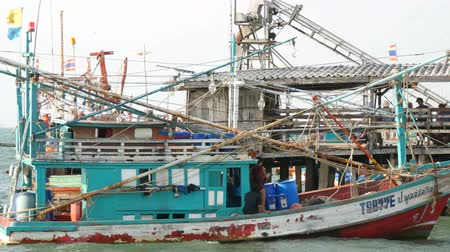 копье : PATTAYA, THAILAND - DECEMBER 25, 2017: Old wooden boat on the dock. Fishermen sort out the networks with a catch on the pier