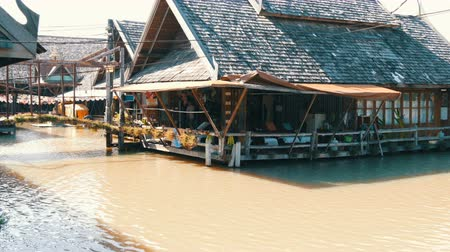 каноэ : PATTAYA, THAILAND - December 18, 2017: A wooden house standing on a river of brown color. House on water in Thailand, on the floating market