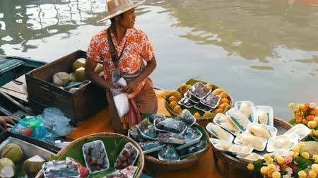 manga : PATTAYA, THAILAND - December 18, 2017: Seller in a colorful shirt and a straw hat sells exotic Thai fruits on a boat