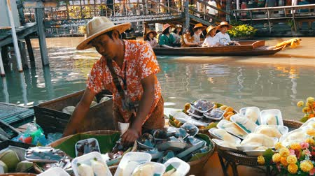 kenu : PATTAYA, THAILAND - December 18, 2017: Seller in a colorful shirt and a straw hat sells exotic Thai fruits on a boat