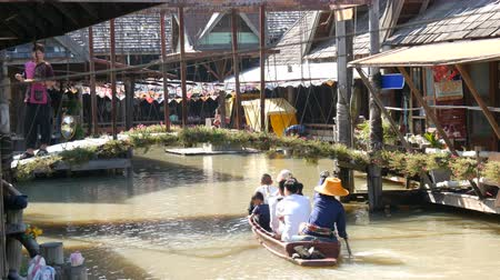 каноэ : PATTAYA, THAILAND - December 18, 2017: Different tourists swim under the bridge go boating on a brown river in Pattaya on floating market
