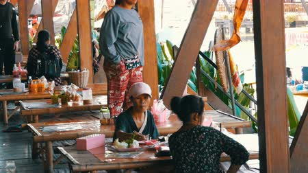 melão : PATTAYA, THAILAND - December 18, 2017: Asian women are eating with bamboo sticks on the shore of picturesque river. Asian style Vídeos