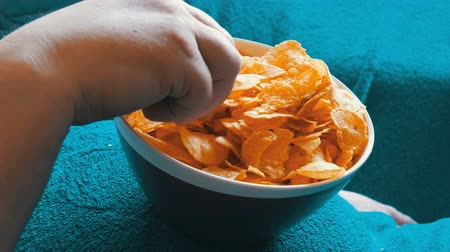 engorda : Married couple lies on a sofa under a blue blanket and eats potato chips from a plate that stands on the big belly of a man. Unhealthy food