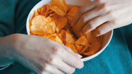 engorda : Large plate with potato chips. The woman lies on the couch and eating potato chips, close up view Stock Footage