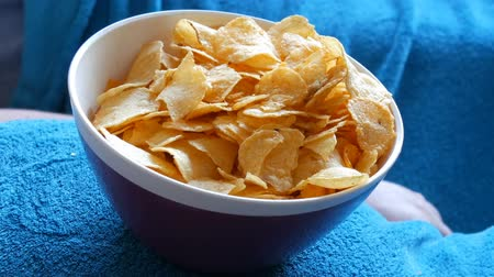 fattening : Married couple lies on a sofa under a blue blanket and eats potato chips from a plate that stands on the big belly of a man. Unhealthy food. Close up view Stock Footage