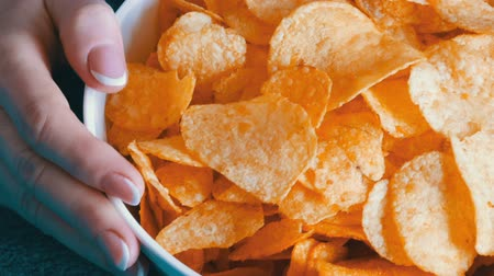 engorda : Beautiful female hands taking potato chips from huge plate, close up view Stock Footage