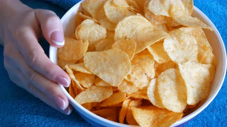 profundidade de campo rasa : Beautiful well-groomed womens hands with French manicure eat potato chips from a huge plate on the couch Stock Footage