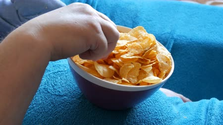 profundidade de campo rasa : Large hand of an elderly man eats potato chips from a huge plate. Mature couple lying on sofa and eating chips. Plate is on a large male abdomen