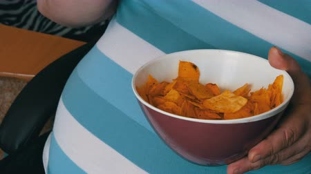 ведущий : Fat, lazy man is eating potato chips sitting on a chair. A huge belly of a man under a striped T-shirt. Fast food, not healthy food