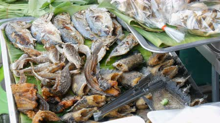 kuşkonmaz : Fried fish lies on the banana leaves. Counter with variety of Thai food. Asian street food