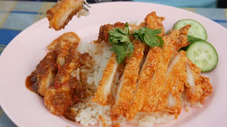 hluboký : A man eats a fork with Thai food. Rice with pea pods and fried crispy chicken on breading