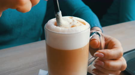latte macchiato : Female hands are stirring the air froth from the latte with straw