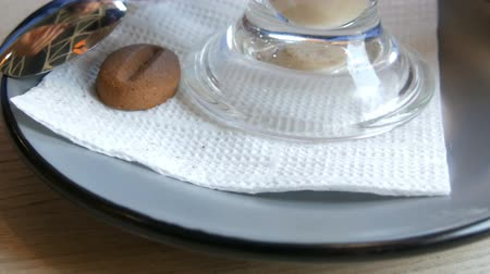 latte macchiato : Woman is turning a saucer and a glass with a latte in a cafe, on the saucer lies a cookie in the form of coffee beans