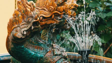 water feature : Three-headed green dragon as a traditional Buddhist symbol. Statue and a fountain of dragon in the garden of Thailand Stock Footage